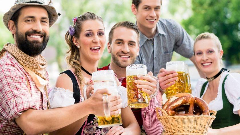 Fünf Teilnehmer in bayrischem Kostüm heben eine Maß Bier