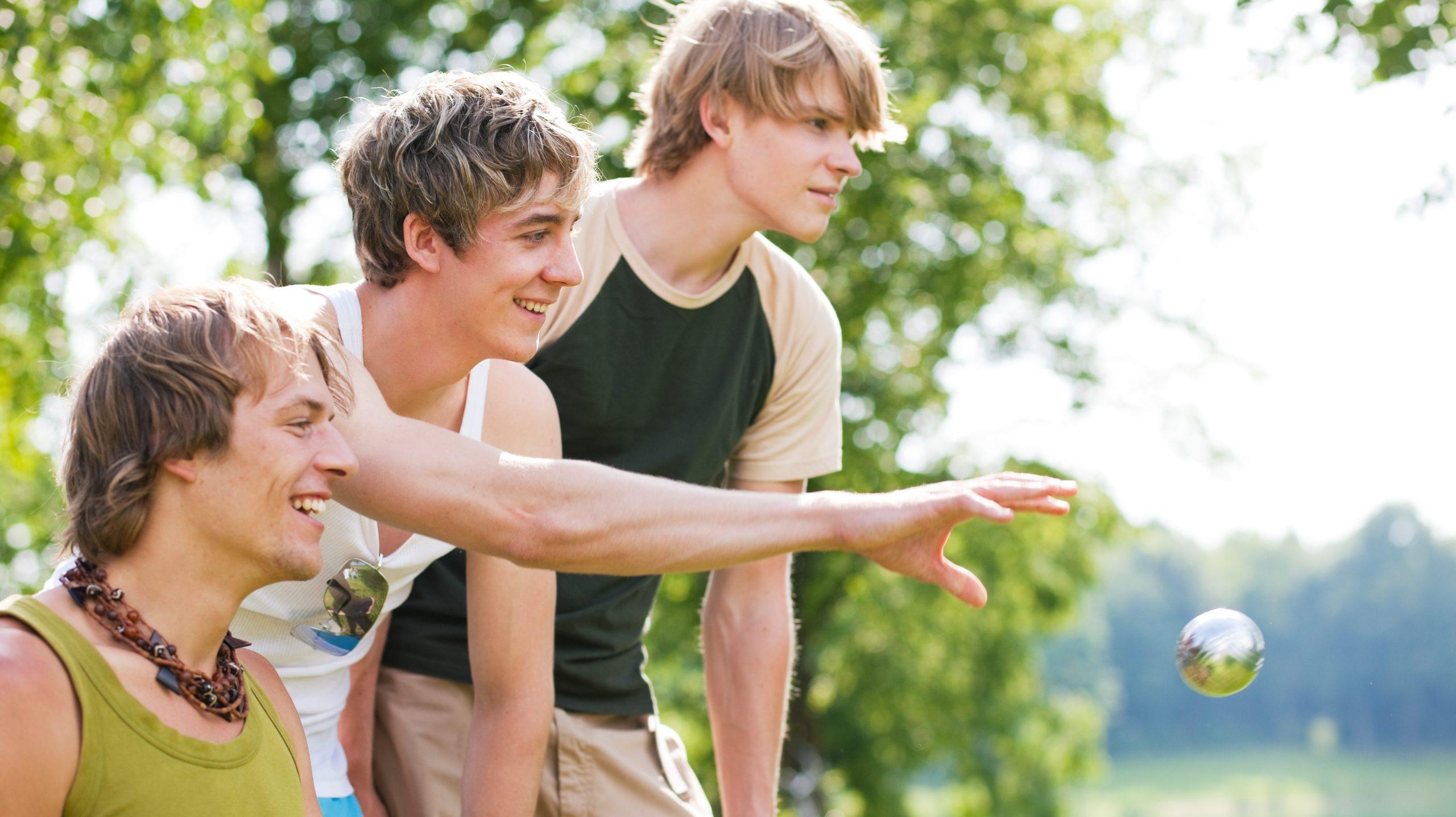 Drei junge Männer spielen Boule