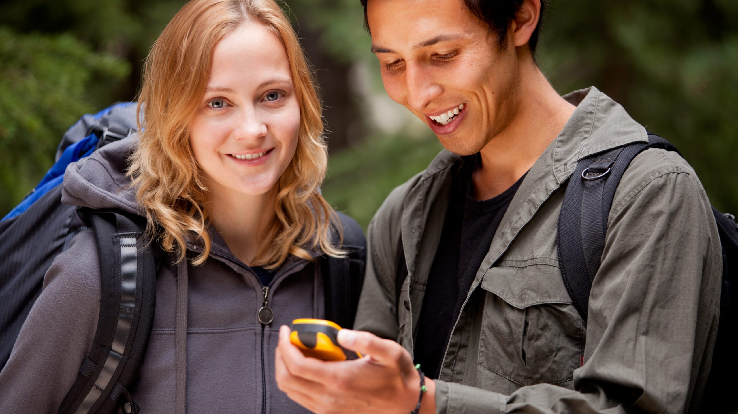 Frau und Mann mit einem GPS-Gerät beim Geocaching