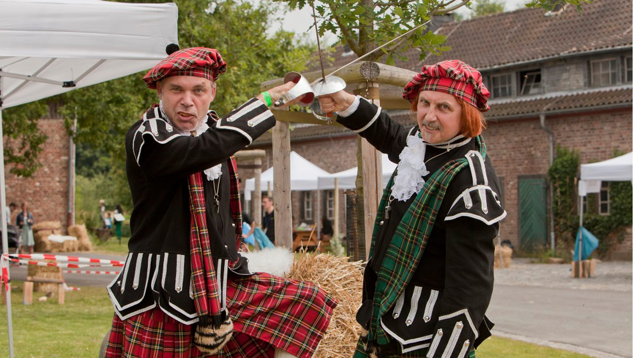 Zwei Teilnehmer der Highland-Games kreuzen in historischen Kostümen die Säbel