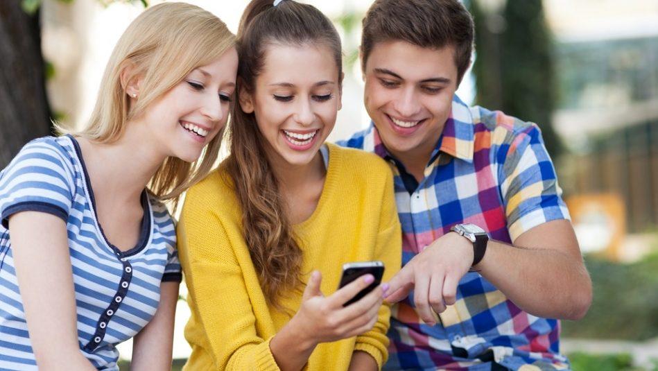 Drei junge Menschen schauen auf ein Handy